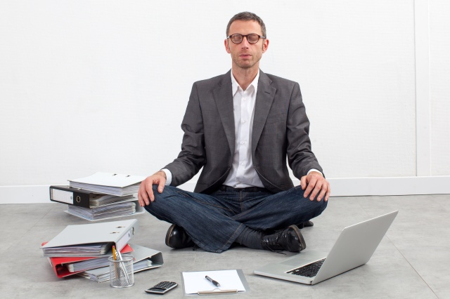 serene businessman meditating at the office, sitting crossed legs