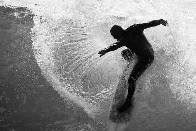 grayscale photo of man on surfboard
